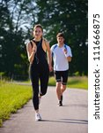 young couple jogging in park at ... | Shutterstock . vector #111666875