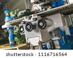 Heavy Duty Lathe Machinery Operator. Caucasian Metalworking Industry Worker in Front of the Machine. - stock photo