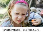 a grumpy young girl sitting at... | Shutterstock . vector #1117065671