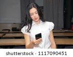cute schoolgirl using phone in... | Shutterstock . vector #1117090451