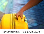 Small photo of Woman takes yellow suitcase Arrived on vacation at a resort. Hand take luggage carrier