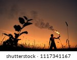 a man with a torch at sunset.... | Shutterstock . vector #1117341167