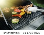 young man grilling some meat... | Shutterstock . vector #1117374527