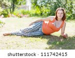 pregnant woman on grass in  summer park - stock photo