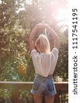Small photo of Back view of young woman vacationer standing on terrace and stretching her hands.
