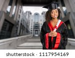 Small photo of Portrait beautiful Asian graduate smile graduated, Student girl young woman in cap gown holding diploma scroll in hand. Celebrating graduation ceremony concept.