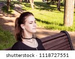 beautiful girl sits on a park... | Shutterstock . vector #1118727551