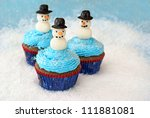 Chocolate cupcakes with vanilla frosting decorated with snowmen made of fondant and rolled in sugar. - stock photo