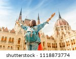 Small photo of Happy asian casual woman student enjoying great view of the Parliament building in Budapest city, travel in Europe concept