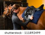 Woman Saddle A Horse In The...