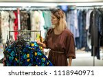 young woman choosing clothes in ... | Shutterstock . vector #1118940971