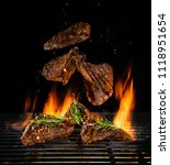 flying beef steaks on grill... | Shutterstock . vector #1118951654