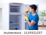 man cleaning fridge in hygiene... | Shutterstock . vector #1119321257