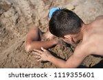 boy buried in the sand beach | Shutterstock . vector #1119355601