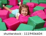 cute girl playing among soft... | Shutterstock . vector #1119406604
