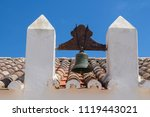 Small photo of Roof of an old church of Nossa Senhora da Rocha in Porches, Algarve, Portugal. Orange old roof tiles. Belfry with a bell. Bright blue sky in the background.