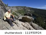 Senior Man Sitting On Cliff An...
