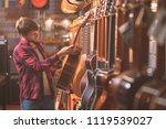 a young man choosing a guitar... | Shutterstock . vector #1119539027