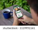 man holding phone with app... | Shutterstock . vector #1119951161