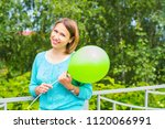 young smiling woman in the park ...   Shutterstock . vector #1120066991