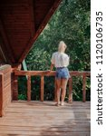 Small photo of Back view of young woman vacationer standing on terrace and enjoying summertime.