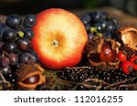 autumnal picture of an apple with chestnuts and other autumnal fruits - stock photo