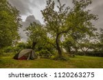 Small photo of Small tent in orchard under cloudy sky. Well camouflaged and blending in environment