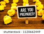 Small photo of Handwriting text writing Are You Prepared Question. Concept meaning Ready Preparedness Readiness Assessment Evaluation White text black paint wooden board clip desk yellow paper notes warning.