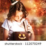 Halloween Cute Little Witch Opening a Box - stock photo