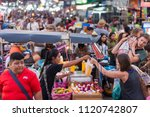 Small photo of BANGKOK, MARCH 11: Tourists haggle with a Pad Thai vendor on Bangkok's Khao San Road on March 11, 2018.