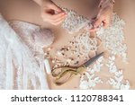 Small photo of close-up hands of woman seamstress tailor ( dressmaker) designer wedding dress sews beads to lace on a blue background in the studio