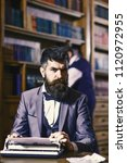 Small photo of Writers routine concept. Writer working on new book with bookshelves on background. Author types novel or poem. Man with beard and strict face sit in library and work with typewriter, close up.