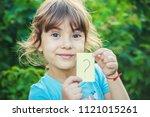 a child holding a sheet of...   Shutterstock . vector #1121015261