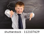Cute preschooler against dark blackboard in classroom - stock photo