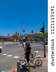 Small photo of Tel Aviv-Yafo, Israel - June 9, 2018: Unidentified biker waiting to get across at Rabin Square im Tel Aviv. Biking is a popular mode of transportation in tel Aviv as well as other cities of Israel.