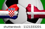 Flags of Croatia and Denmark painted on two clenched fists facing each other with closeup 3d soccer ball in the background/Mixed media football match concept