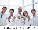 group of doctors hold their... | Shutterstock . vector #1121386187