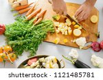 man cuts vegetables for cooking ... | Shutterstock . vector #1121485781