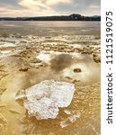 Small photo of Winter natural wonder. Yellow pieces of snow melting on beach. Wonderful nature creation.