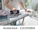 woman ironing clothes using... | Shutterstock . vector #1121552834
