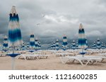 closed beach sunshades on the... | Shutterstock . vector #1121600285