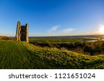 Small photo of Hadleigh Castle, Essex, England on the left with the sunsetting on the right clear blue sky with backlit grass fisheye lens