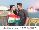 Happy young couple with hungarian flag looking to each other at Budapest, Hungary