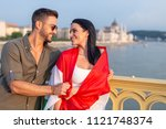Man covering happy woman with hungarian flag at Budapest, looking to each other, Hungary