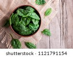 fresh spinach leaves in a bowl... | Shutterstock . vector #1121791154