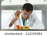 Indian male scientific researcher looking at a flask of liquid in a laboratory. - stock photo