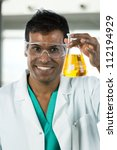 Portrait version of an Indian scientist looking at beaker of liquid in a lab. - stock photo