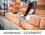 Small photo of Bricklayer industrial worker installing brick masonry on exterior wall with trowel putty knife