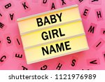 Small photo of Choosing baby girl name concept with lightbox and various letters scattered around