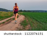Small photo of Athletic Blonde Teenage Girl Running At Dirt road In field. Sport girl running outdoor. Young woman running in field. Back view running lass on meadow at sunset. Fitness training.